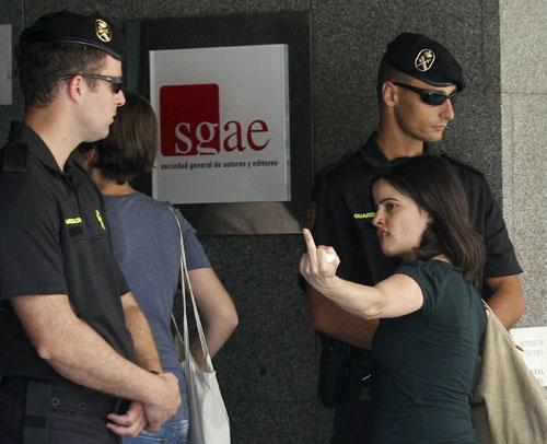Una trabajadora de la SGAE ante dos guardias civiles en la entrada de la sede de la Sociedad General de Autores y Editores. © EFE/Ángel Díaz