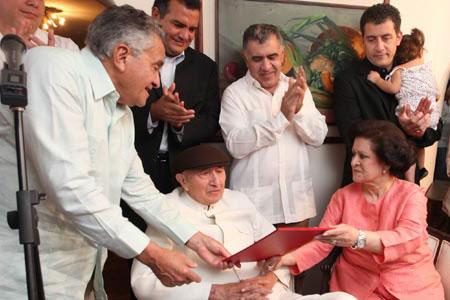 el presidente de la Asamblea Nacional, Fernando Soto Rojas, entrega la distinción al Tío Simón.