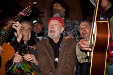 El veterano músico y activista Pete Seeger, de 92 años, al centro, canta ante una muchedumbre de casi 1.000 manifestantes que respaldan el movimiento Ocupemos Wall Street en el Columbus Circle, en Nueva York, el sábado, 22 de octubre del 2011. © John Minchillo/AP