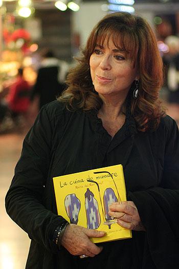 Maria del Mar Bonet sosteniendo un ejemplar de «La cuina de mumare» en el Mercado de la Llibertat en Gràcia (Barcelona). © Xavier Pintanel