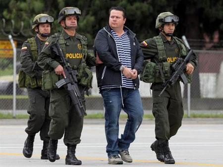 Alejandro Jiménez, alias «El Palidejo» es ecoltado por tres policías colombianos. © EFE
