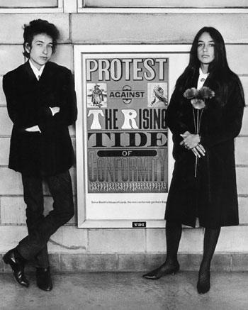 Bob Dylan y Joan Baez delante de un cartel contestatario, aeropuerto de Newark, Nueva Jersey, 1964  © Daniel Kramer