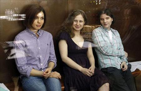 Las tres integrantes del grupo de punk «Pussy Riot» Nadezhda Tolokónnikova (izq), Yekaterina Samutsévich (der) y Maria Aliókhina (c) se sientan en el banquillo de los acusados en una zona acristalada, a la espera de que comience la sesión de juicio en el juzgado del distrito Khamovnichesky en Moscú, Rusia. © EFE