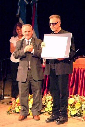 León Gieco recibe de manos del rector de la Universidad Nacional de Entre Ríos, Jorge Gerard, el título de Doctor Honoris Causa.