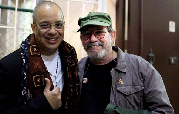 El cantautor cubano Silvio Rodríguez, a la derecha, posa con su compatriota y músico Issac Delgado, que vive en Estados Unidos, luego de que el veterano lo invitara cantar en el escenario de un barrio popular de La Habana, el viernes 29 de marzo de 2013. © Franklin Reyes