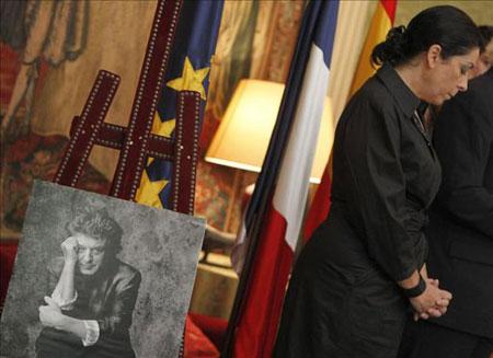 La viuda de Enrique Morente, vestida por entero de negro y flanqueada por un retrato de su marido fallecido. © EFE