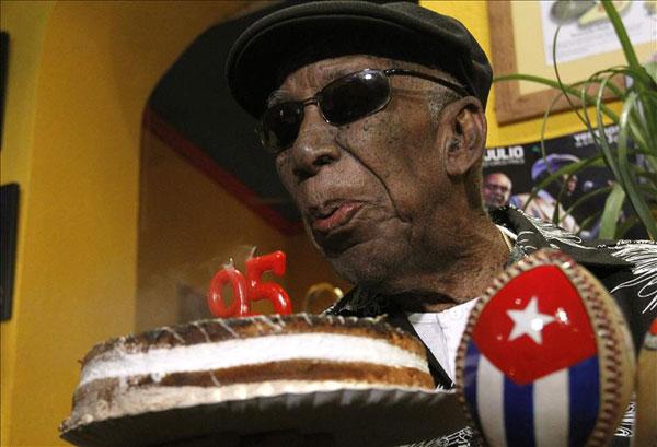 El cantante de la Vieja Trova Santiaguera, Reinaldo Creagh, sopla las velas de su 95 cumpleaños, que hoy ha celebrado tomando mojitos con varios periodistas en un bar del madrileño barrio de Lavapiés. © EFE
