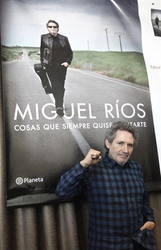 Miguel Ríos posando ante la portada de su libro. © EP