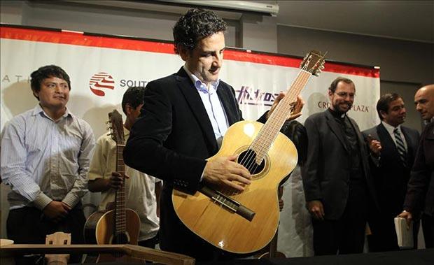 El tenor peruano Juan Diego Flórez (c) fue registrado este lunes al tocar una guitarra, junto a unos niños pertenecientes a su proyecto social Sinfonía por el Perú, en Lima (Perú). © EFE