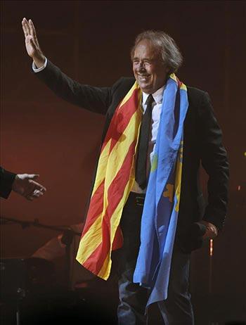 El cantante catalán Joan Manuel Serrat se despide del público envuelto en las banderas catalana y asturiana. © EFE
