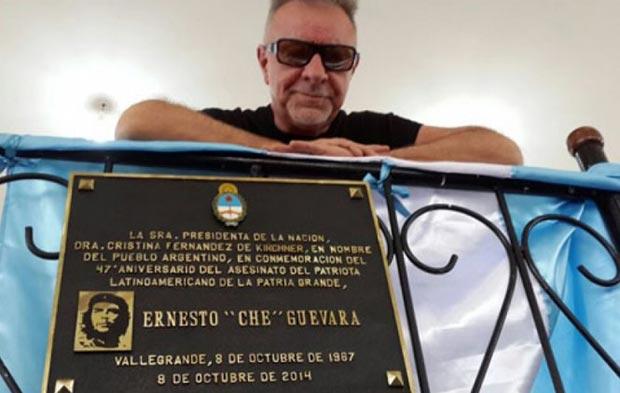 León Gieco tras la placa que recuerda el asesinato del Che Guevara en Vallegrande (Bolivia).
