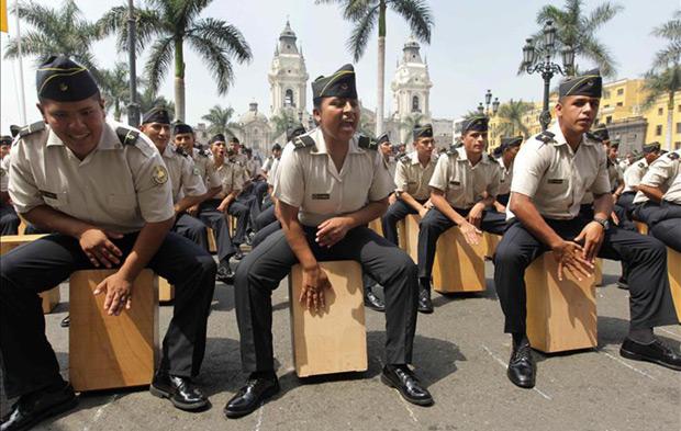Alumnos de la escuela de policía participan en la octava edición del Festival Internacional del Cajón Peruano que arrancó este sábado 25 de abril de 2015, con una multitudinaria «cajoneada» en la Plaza de Armas de Lima para homenajear al fallecido músico Rafael Santa Cruz. © EFE