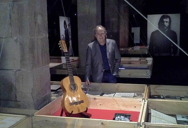 Joan Manuel Serrat posa ante su primera guitarra, aquella que estaba «bruta i trencada» (rota y sucia) y que ahora está completamente restaurada. © Xavier Pintanel