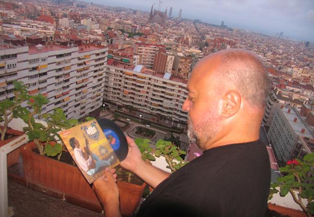 Fermí Puig en la terraza de su casa observando el primer single de su colección, el «Mig amic» (Vergara, 1968) de Peret. Al fondo, la Barcelona que tanto ha cantado Serrat. © Manel Gausachs
