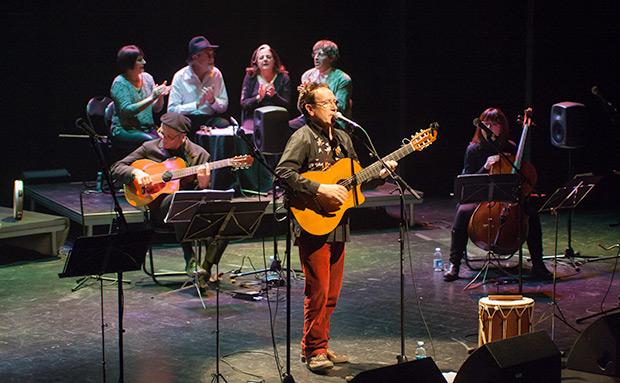 Detrás de Eliseo Parra, Jordi Fusté, «Lo Mut de Ferreries», a la guitarra. Más al fondo, esperando el turno para cantar. © Xavier Pintanel