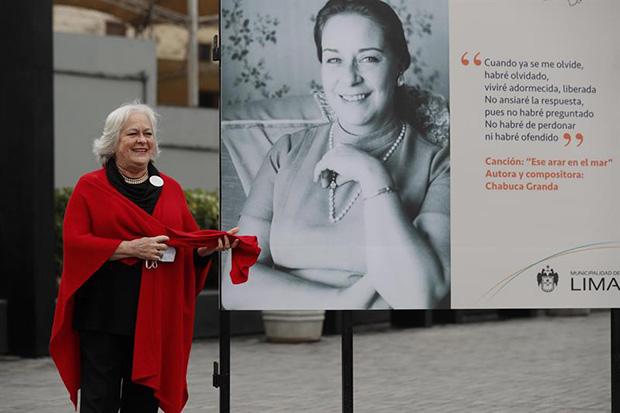 Teresa Fuller, hija de Chabuca Granda, posa junto a un retrato de su madre el 2 de septiembre de 2020 en la Alameda Chabuca Granda, en el centro de Lima (Perú). © EFE/Paolo Aguilar